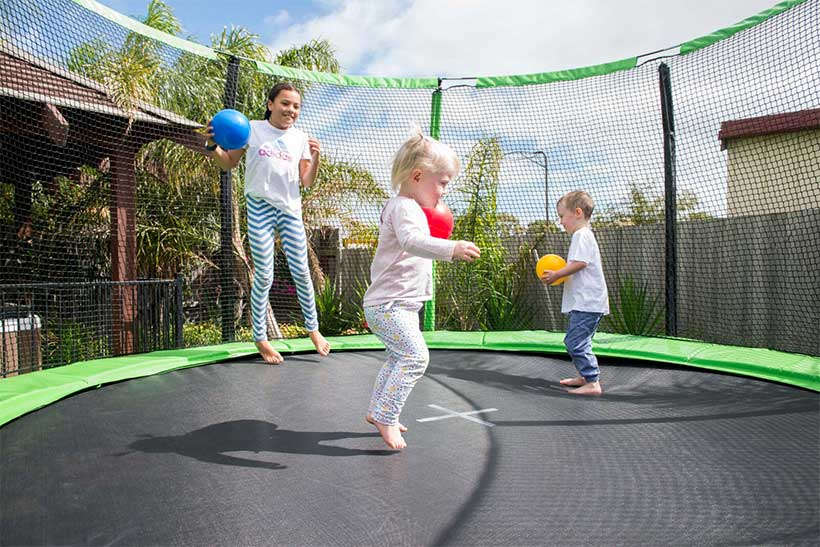 three kids jumping on a trampoline with a safety net