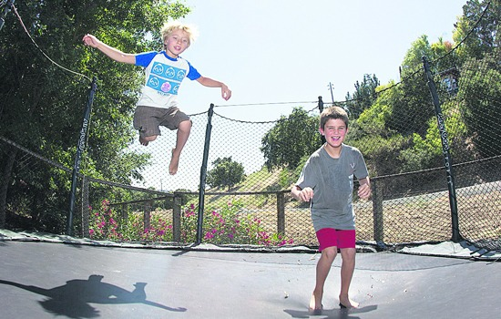 kids playing on a double trampoline