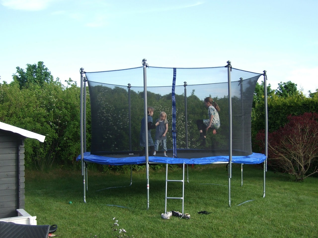 Children playing on the trampoline in backyard