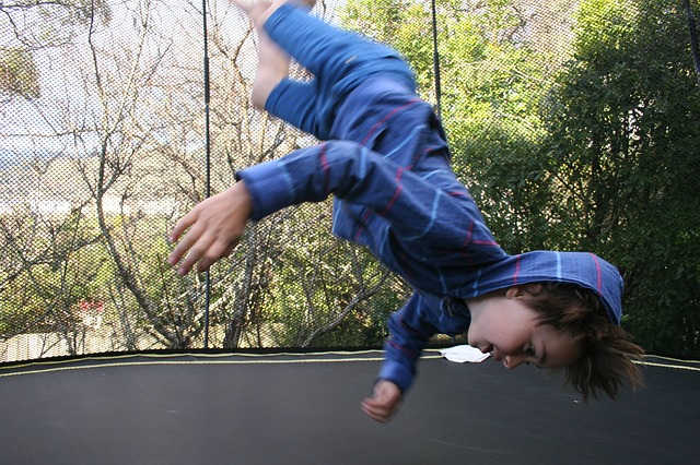 young boy doing a flip on trampoline failing