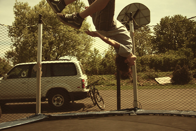 image of a young boy doing flip on trampoline